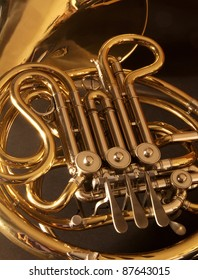 A close up of a very golden, concert french horn