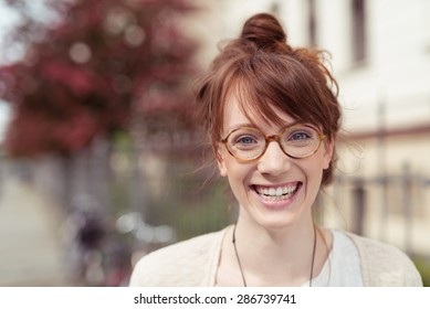 Close up Very Happy Pretty Young Woman Wearing Round Eyeglasses, Showing Toothy Smile at the Camera.
