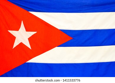 Close up of a vibrant color Cuban National Flag. The patriotic symbol has a red triangle with a white star in the center. Three blue and two white stripes. Full frame image