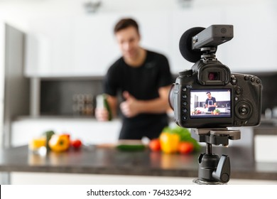Close up of a video camera filming young smiling male blogger at the kitchen