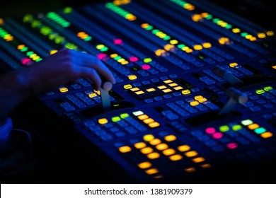 Close Up of a Video Control Switcher Board with brightlyColored Lights in a dark control room in a media center