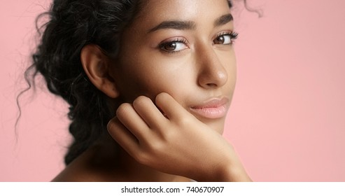 Close up video of a happy and relaxed young woman with perfect olive skin fixing her wavy black hair isolated on white