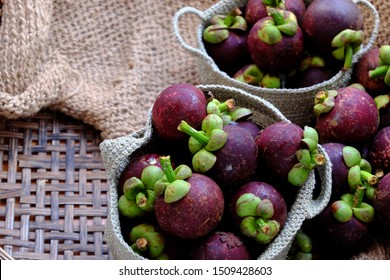 Close up Vietnamese tropical fruits in knitted handbag on burlap background, fresh Mangosteens fruit