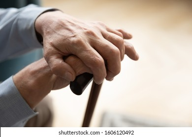 Close up view 60s lovely male hands holding cane. Parkinson disease, nursing home for elderly, abandoned aged human existence with pain and miserable life, difficult to moving without support concept
