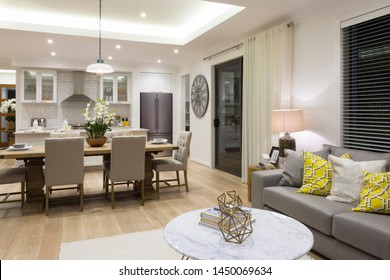 A close view of adjoined kitchen, dining area and a living room with well-defined furnishing, ambient lighting and modern interior design.