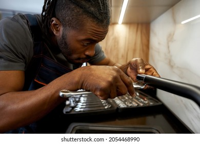 Close view African American handyman fixing kitchen tap using spanner. Handsome young plumber concentrated on kitchen tap troubleshooting. Authenticity in business.