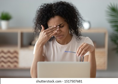 Close up view african unhappy woman sitting near computer take break during workday took off glasses frown face feel unhealthy, closed eyes to relief painful sensations dry tensed eye strain concept