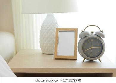 Nahe Blick auf den Wecker auf dem Tisch neben dem weißen gemütlichen Bett im Schlafzimmer.