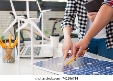 close up view of alternative energy engineer pointing to a solar power panel and discussion team for the future power in the studio