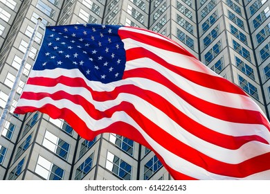 Close up view of a American flag flying in the wind with a downtown skyscraper background.