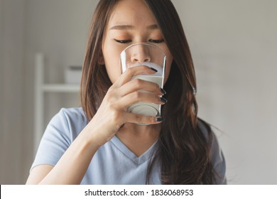 Close up view of asian woman drinking milk.
