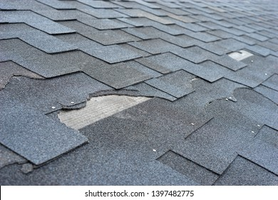 Close up view of asphalt shingles roof damage that needs repair.