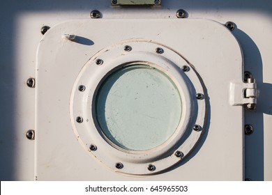 Close up view of aTall Ships metal door with round window.