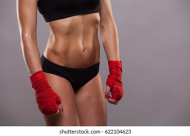 Close view of athletic girl posing in red bandages, isolated on the grey background boxing fighter kickbox