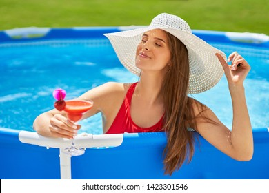 Close up view of attractive woman relaxing on swimming pool in the backyard
