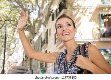 Close up view of an attractive young businesswoman raising her arm to call a taxi in a busy city, outdoors.