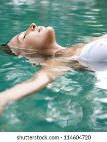 Close up view of an attractive young woman floating on a spa's swimming pool, smiling.