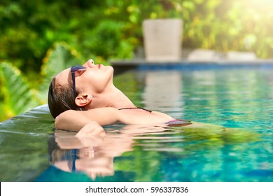 Close up view of an attractive young woman relaxing on a spa's swimming pool.Travel, happiness emotion, summer holiday concept.