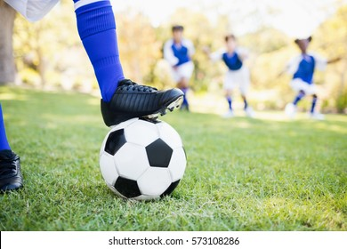 Close up view of balloon under football boots against children playing background in park