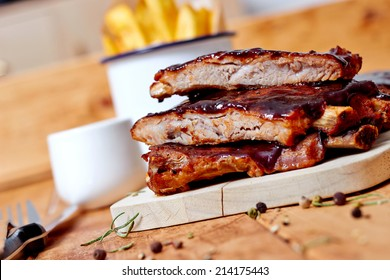 Close up view of barbecue ribs with fries and sauce on a old wooden table