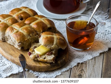 Close up view of a batch of Hot Cross buns with one bun ready for eating with a pad of melted butter. Served with hot tea.