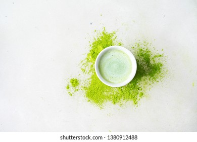 Close view of bawl with Japanese Matcha tea over scattered  powder tea on concrete background with copy space, top view.