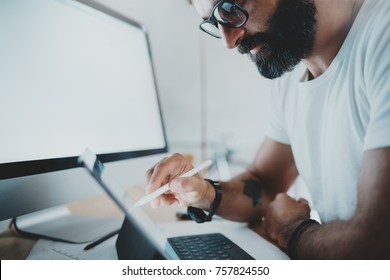 Close up view of bearded man in white tshirt working with portable tablet computer.Designer drawing digital plans at modern lightful office.Horizontal.Blurred background.Cropped