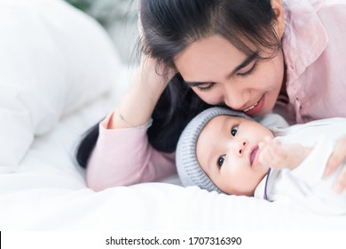 Close up view of beautiful Asian mother and her cheerful lovely newborn baby boy. Mother holding baby hand with warm touch, kiss kid head, talking with infant with smiling face. Happy family concept.