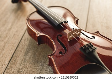 Close up view of beautiful classical violin lying on wooden background. Musical instruments. Music equipment. Music background