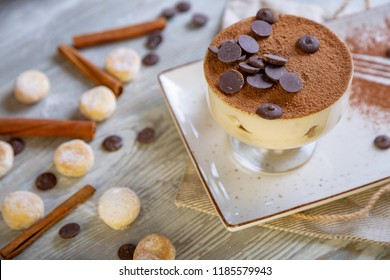 Close up view of beautiful elegant sweet dessert, tiramisu, served on the plate. Beautiful decoration, restaurant dish, ready to eat. Tea time, cozy atmosphere.