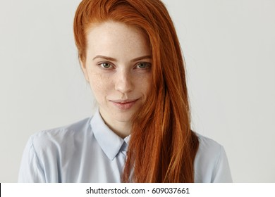 Close up view of beautiful happy Caucasian woman with ginger hair and freckles looking and smiling at camera with enigmatic inscrutable smile at studio wall. People, youth and happiness concept