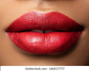 Nahaufnahme von schönen Frauenlippen mit rotem Lippenstift. Mode macht sich das aus. Konzept für Kosmetologie, Drogerie oder Mode-Make-up. Studioaufnahme