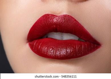 Close up view of beautiful woman lips with red matt lipstick. Cosmetology, drugstore or fashion makeup concept. Beauty studio shot.