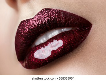 Close up view of beautiful woman lips with dark red lipstick. Fashion make up. Studio shot