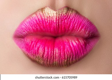 Close up view of beautiful woman lips blowing a kiss. Modern pink and gold makeup. Studio shot. Lips cosmetics, healthy skin and tooth, modern makeup or happy woman concept