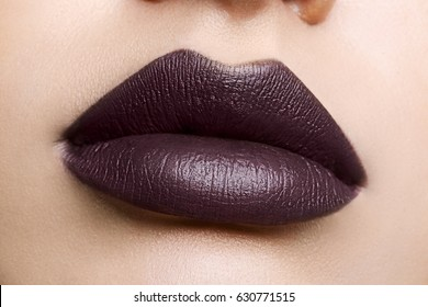 Close up view of beautiful woman lips with purple matte lipstick. Cosmetology, drugstore or fashion makeup concept. Passionate kiss