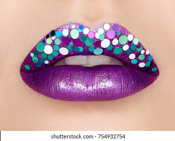 Close up view of Beautiful Woman Lips with Purple Lipstick. Open Mouth with white Teeth. Cosmetology, drugstore or Fashion Makeup Concept.  Beauty studio shot.