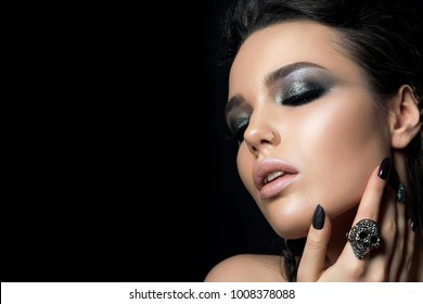 Close up view of beautiful woman touching her face. Perfect skin and evening makeup. Studio shot. Sensuality, passion, trendy youth makeup or cosmetology concept. Copy space