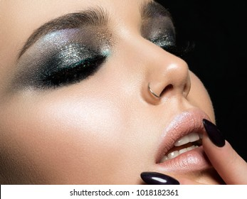 Close up view of beautiful woman touching her lips. Perfect skin and evening makeup. Macro studio shot. Sensuality, passion, cosmetology, lip care, plastic surgery or injection concept.