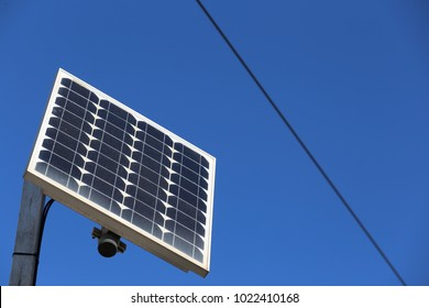 Close up view from bellow of a solar panel used to supply electricity to a traffic light. Square element fixed at the top of pole in a city in France. Blue clear sky in background with part of cables