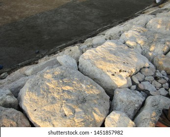 Close up view of big huge stone rocks, flat lay heap pile lined row be breakwater poles long near edge coast shore beach ocean use for cut waves. Safe concept stony surround dock, port, lagoon, pier