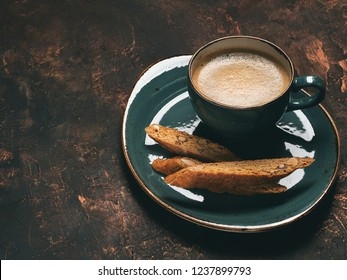 Close view of biscotti cookies with almonds and one cup of coffee espresso on dark copper background