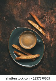 Close view of biscotti cookies with almonds and one cup of coffee espresso on dark copper background, top view, vertical composition.