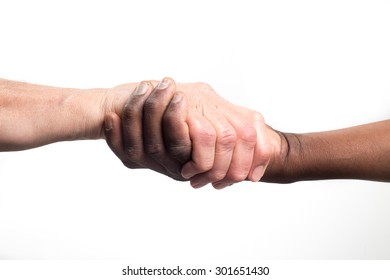 Close up view of a black / african man and a white / caucasian man shaking hands from below