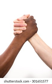 Close up view of a black / african man and a white / caucasian man gripping hands