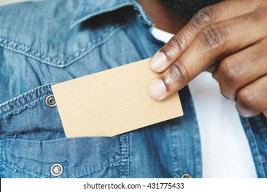 Close up view of black male holding blank card. Young African businessman pulling out business card from pocket of his denim jacket, exchanging information with a potential partner. Film effect