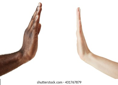 Close up view of black male and white female hands giving a five isolated against white studio wall, symbolizing multicultural cooperation and interracial friendship. Peace and unity against racism.