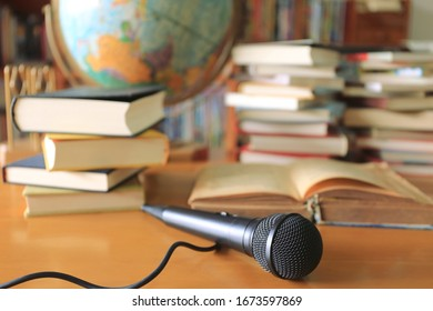 A close up view of a black microphone in the classroom Stacks of books and globes in the background selective focus and shallow depth of field
