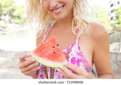 Close up view of blond woman hands holding piece watermelon on summer beach holiday, joyful smiling, outdoors. Healthy eating, wellness vitamins food, well being recreation lifestyle, sunny exterior.