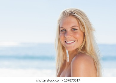 Close up view of blonde woman smiling at camera against ocean